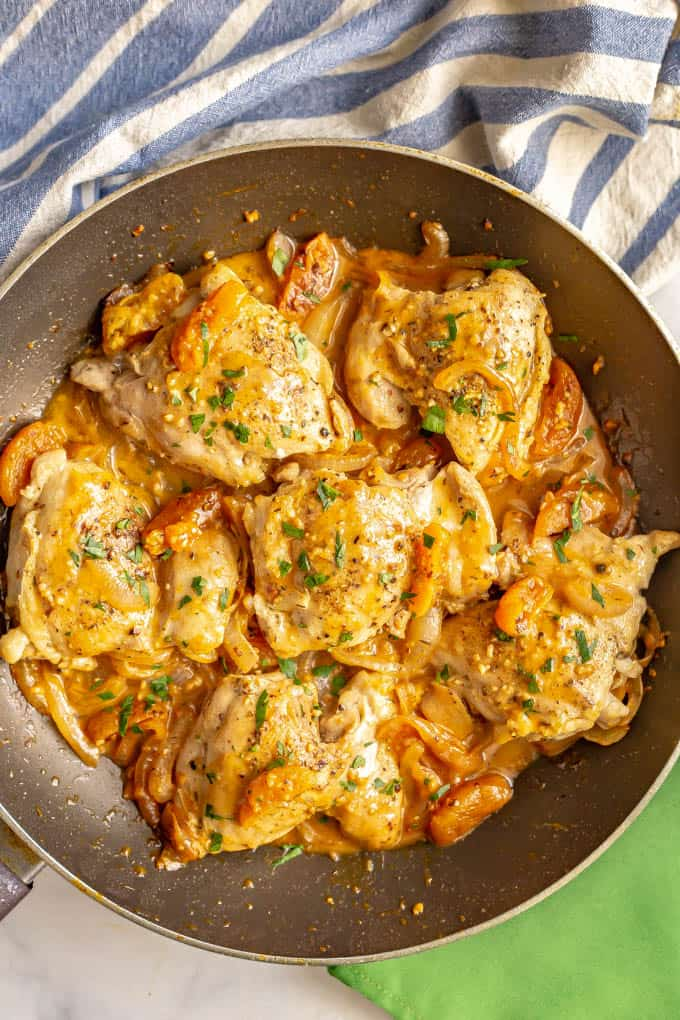 Chicken thighs cooked in a large skillet with a creamy pan sauce of onions, apricots and broth