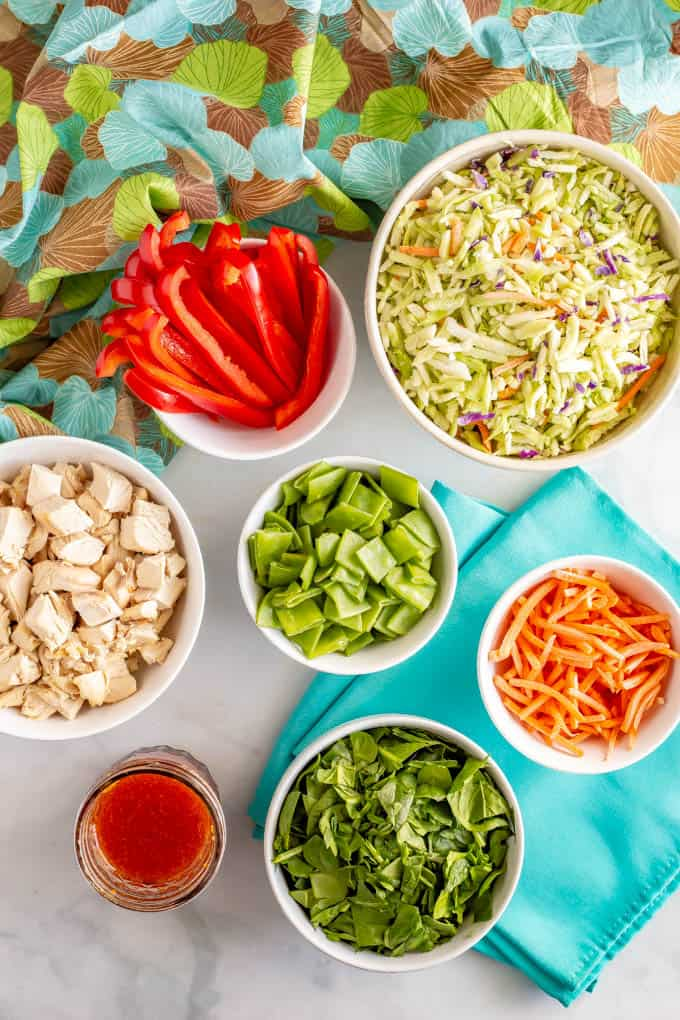 Ingredients for broccoli slaw salad laid out in separate bowls
