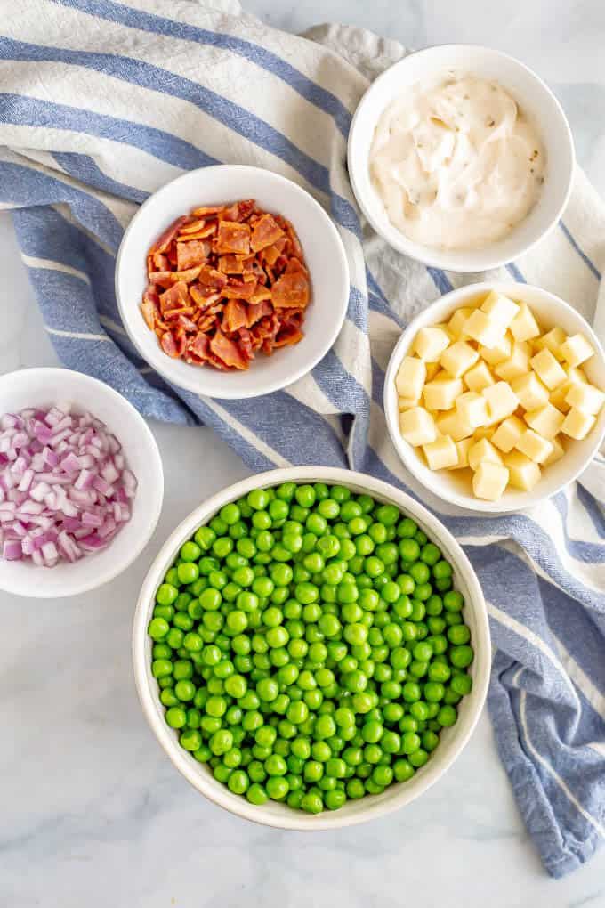 Ingredients for pea salad in separate white bowls with a blue napkin underneath