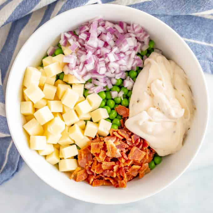 White bowl with ingredients layered in, including peas, cheese, red onion and bacon