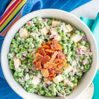 Creamy pea salad with cheddar cheese and bacon in a large white serving bowl