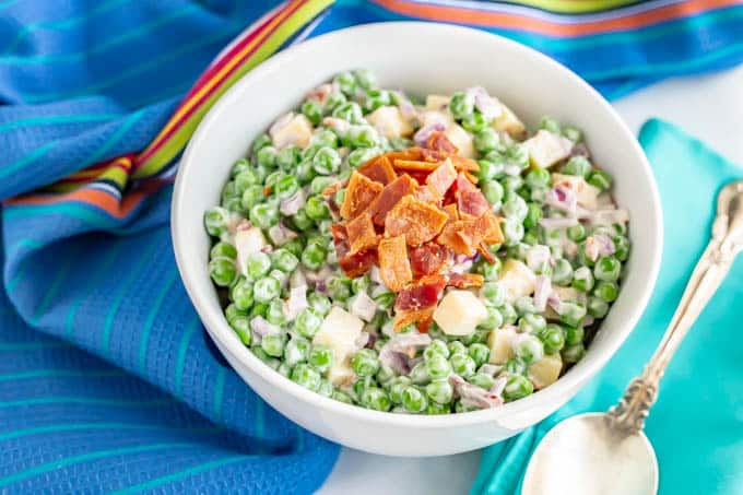 Southern pea salad with bacon on top in a white serving bowl
