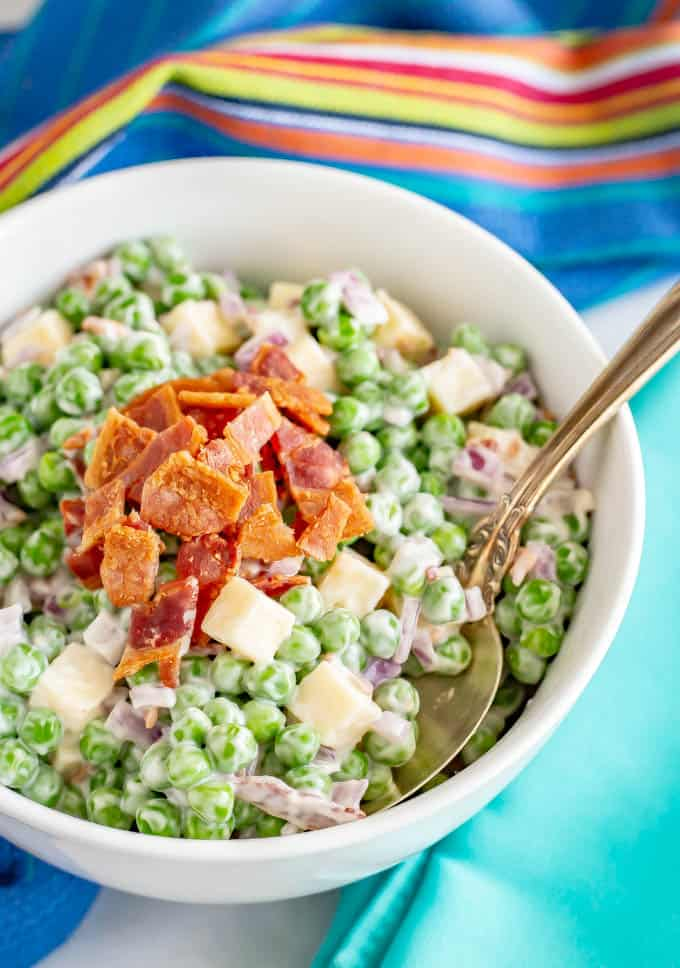 Creamy pea salad with cheddar and bacon is a classic Southern side dish at potlucks and BBQs and easy to make ahead. It's always a hit! #peas #salad #bbqfood #picnicfood #summerfood #summersalad