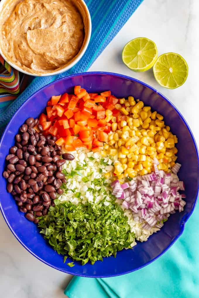 Ingredients to make creamy Mexican style coleslaw recipe arranged in a large blue bowl with taco dressing in a separate bowl