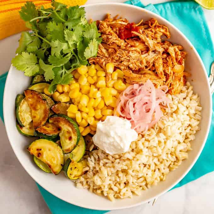 Grain bowl with brown rice, salsa chicken, zucchini and corn