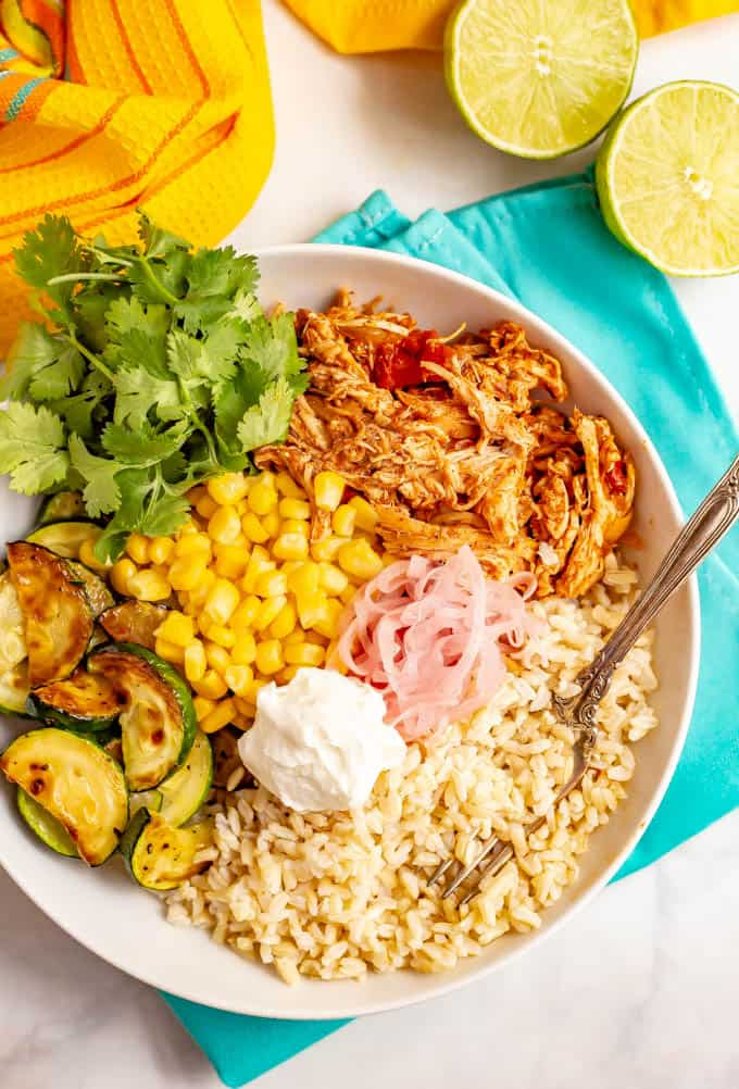 Healthy grain bowl with brown rice, salsa chicken, corn and zucchini, plus toppings in a large white bowl
