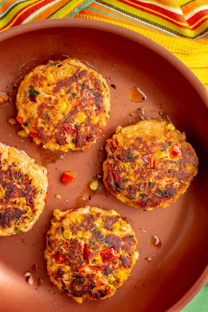 Southwest salmon burgers cooking in a skillet