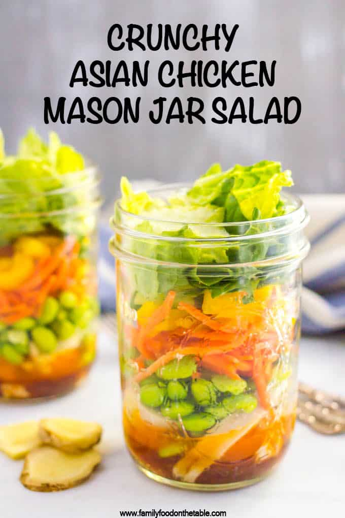 A layered Asian chicken salad in a glass mason jar with edamame, carrots and lettuce and a soy ginger dressing at the bottom
