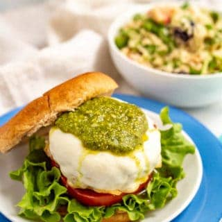 A cheese smothered burger on a bun with pesto, lettuce and tomato and a salad in a bowl in the background