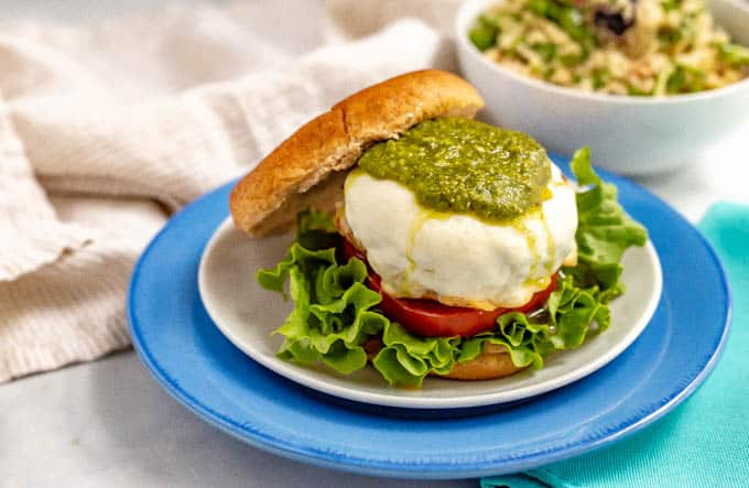 A mozzarella covered chicken burger with pesto on top served on a bun with fixings