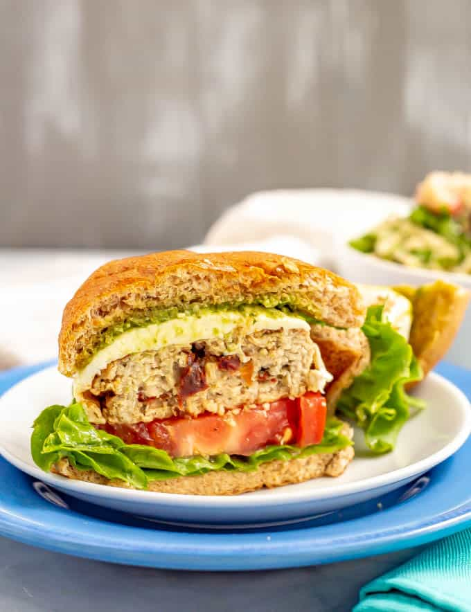 An Italian chicken burger sliced in half and served with lettuce, tomato, mozzarella cheese and pesto on a bun
