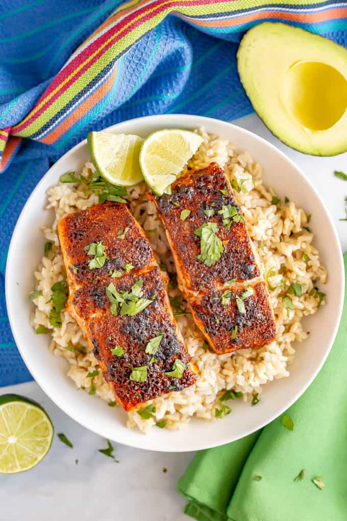 Baked salmon filets over a bed of rice in a white bowl with chopped cilantro