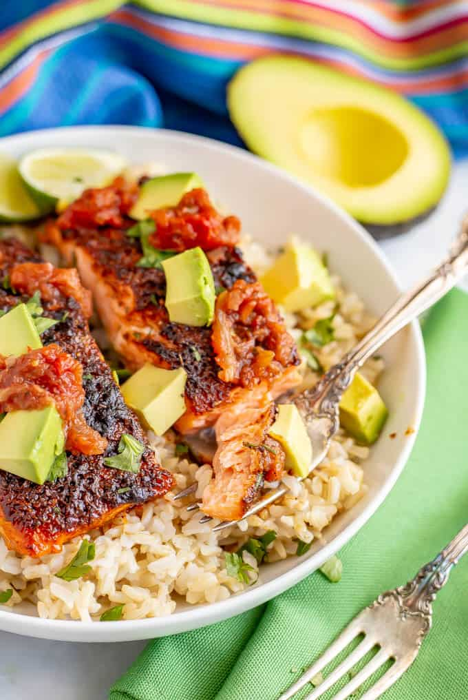 Close up of fork with a bite of roasted salmon topped with salsa and avocado