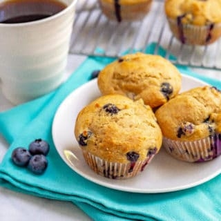 Whole wheat muffins with blueberries on a white plate with coffee and extra blueberries nearby