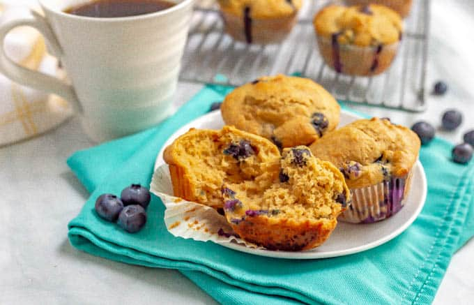 Blueberry muffins on a white plate with coffee and extra muffins on a muffin rack