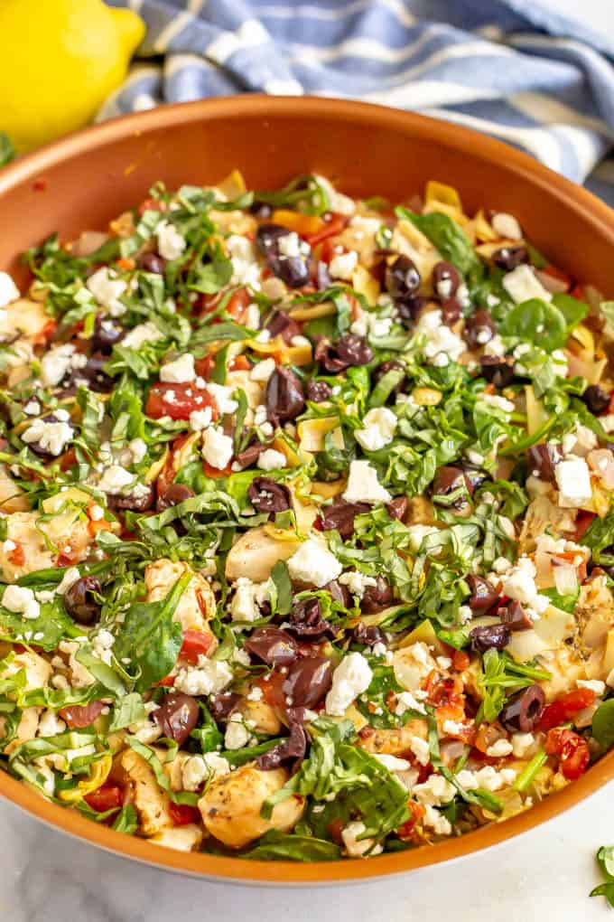 Copper skillet with cooked Mediterranean style chicken, artichokes, tomatoes and spinach with olives and feta on top
