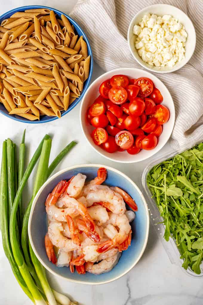 Ingredients laid out in separate bowls, including pasta, shrimp, tomatoes, feta cheese, scallions and arugula