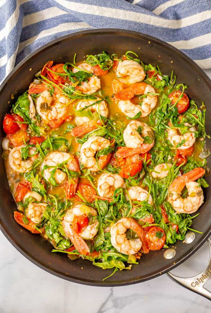 Shrimp, arugula and tomatoes cooking in a large pan with a blue striped kitchen towel nearby