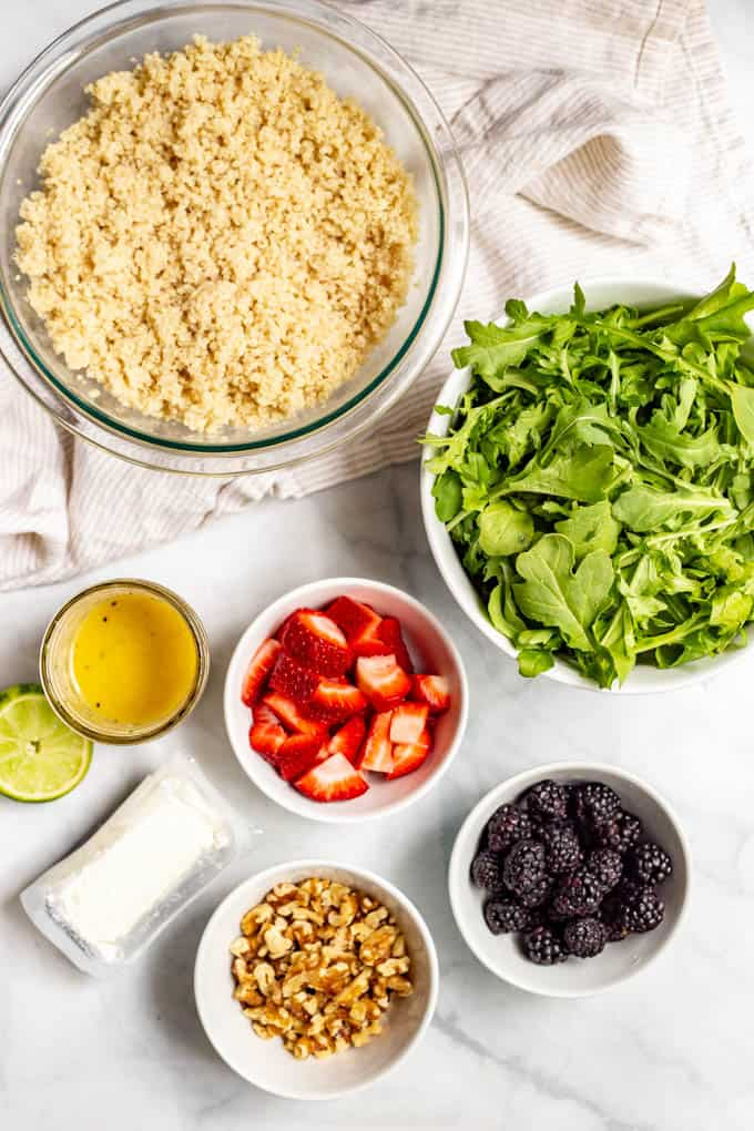Ingredients for summer quinoa salad laid out in separate bowls on a marble countertop