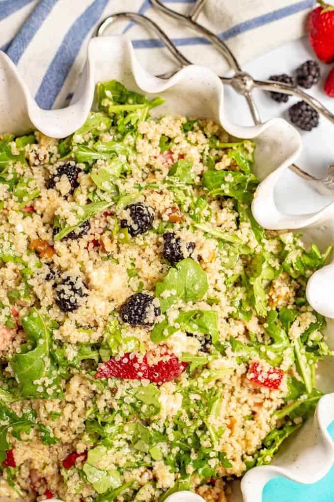 Quinoa, arugula and fresh fruit salad with walnuts and goat cheese in a large white bowl