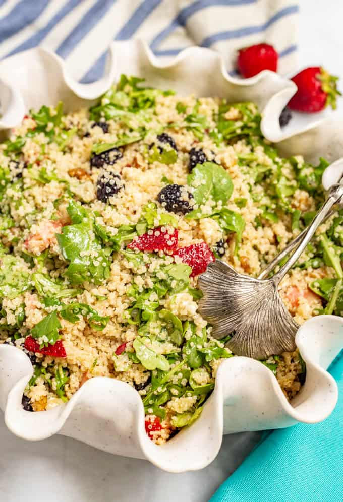 Summer quinoa salad with arugula, fresh berries and goat cheese being served from a large white bowl with a fluted edge