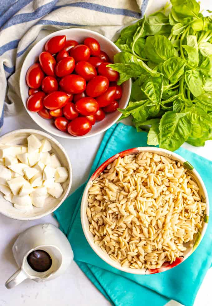 Tomatoes, orzo pasta, mozzarella cheese, basil and balsamic vinaigrette laid out on a table with napkins