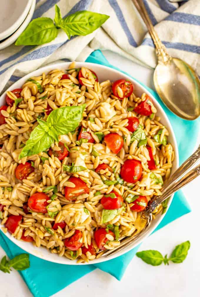 Caprese pasta salad served in a large bowl with two forks in the bowl and fresh basil nearby