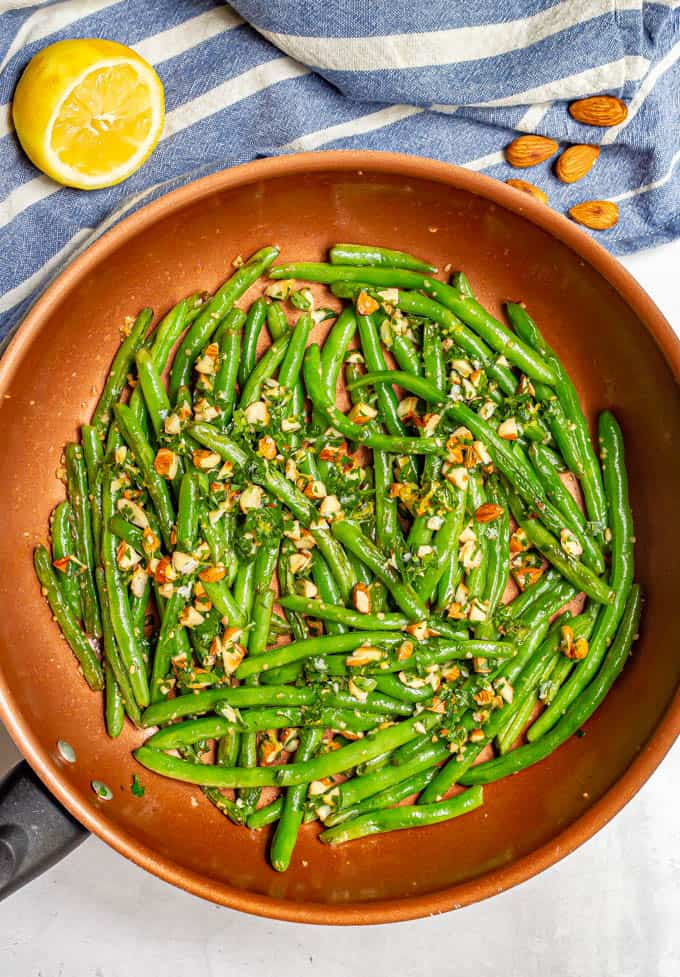 Green beans in a large copper pot after cooking and served with an almondine mixture on top