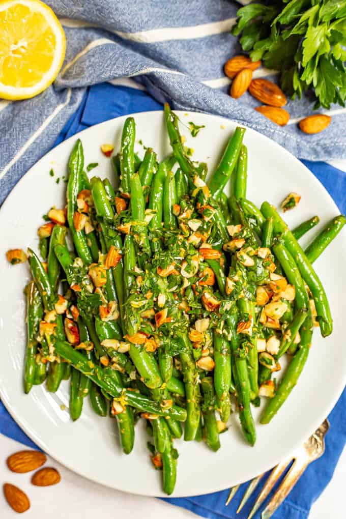 Green beans served on a plate with a sprinkling of almonds mixed with parsley and lemon juice and garnishes nearby