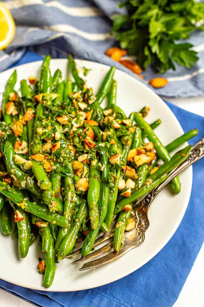 Green beans served on a plate with a sprinkling of almonds mixed with parsley and lemon juice with a fork on the plate