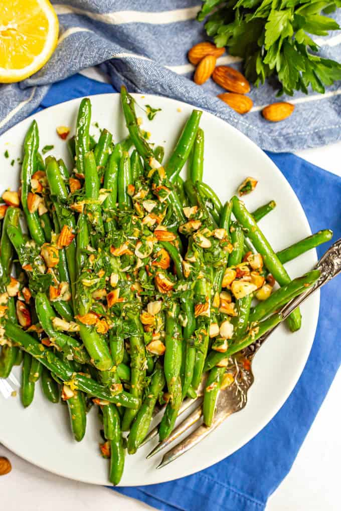 Green beans served on a plate with a sprinkling of almonds mixed with parsley and a fork along the side of the plate