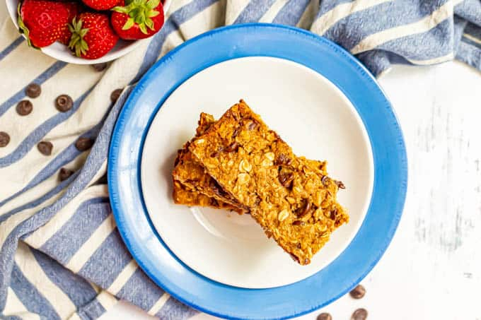 Overhead shot of granola bars stacked on top of each other on a white plate with a blue towel nearby