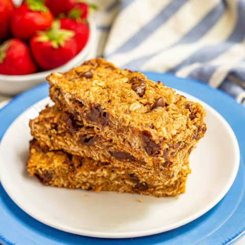Three thick, chewy homemade granola bars stacked on a white plate with strawberries in the background