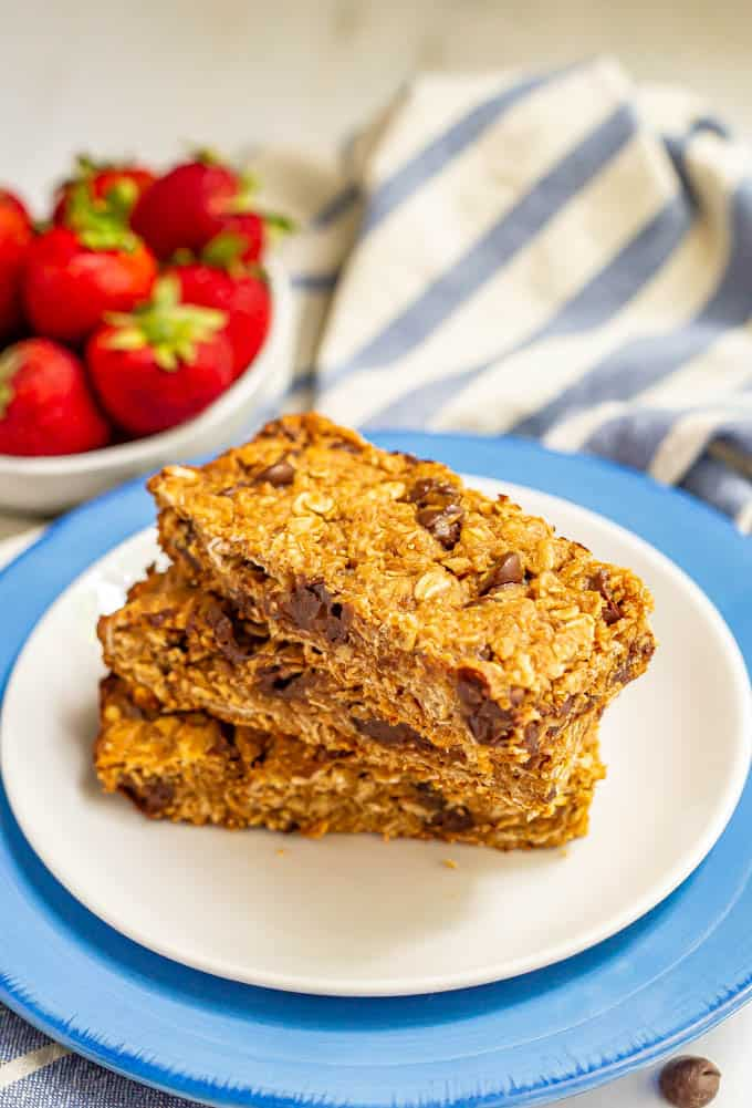 Three chocolate chip granola bars stacked on a plate with a bowl of strawberries in the background