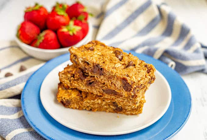 Chocolate chip granola bars stacked on a plate with a bowl of strawberries in the background