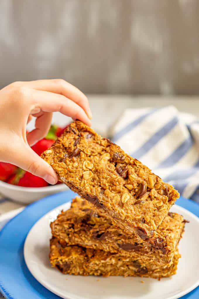 A stack of three granola bars on a plate with one being picked up