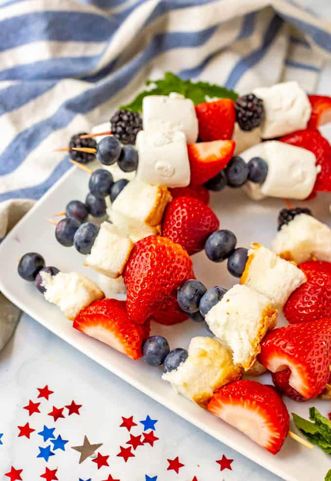 Red white and blue fruit snacks on a white plate with stars on the table for decoration