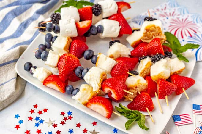 Strawberry, blueberry and angel food cake fruit kabobs on a plate with July 4th decorations