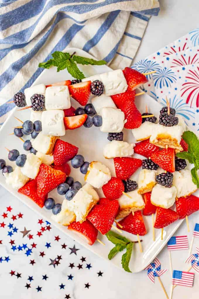 Large fruit kabobs stacked and arranged on a white platter with red white and blue decorations