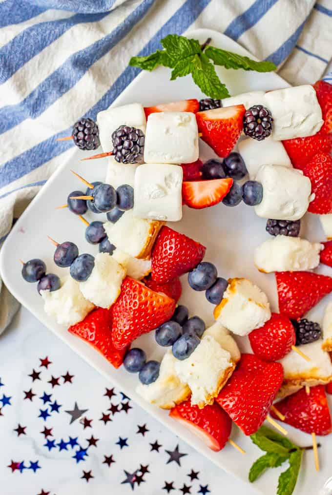 4th of July fruit kabobs stacked and arranged on a white platter with red white and blue decorations