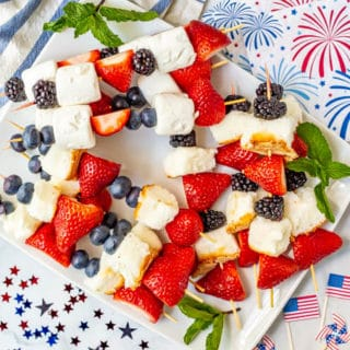 Platter full of red white and blue July 4th fruit kabobs and festive American decor nearby