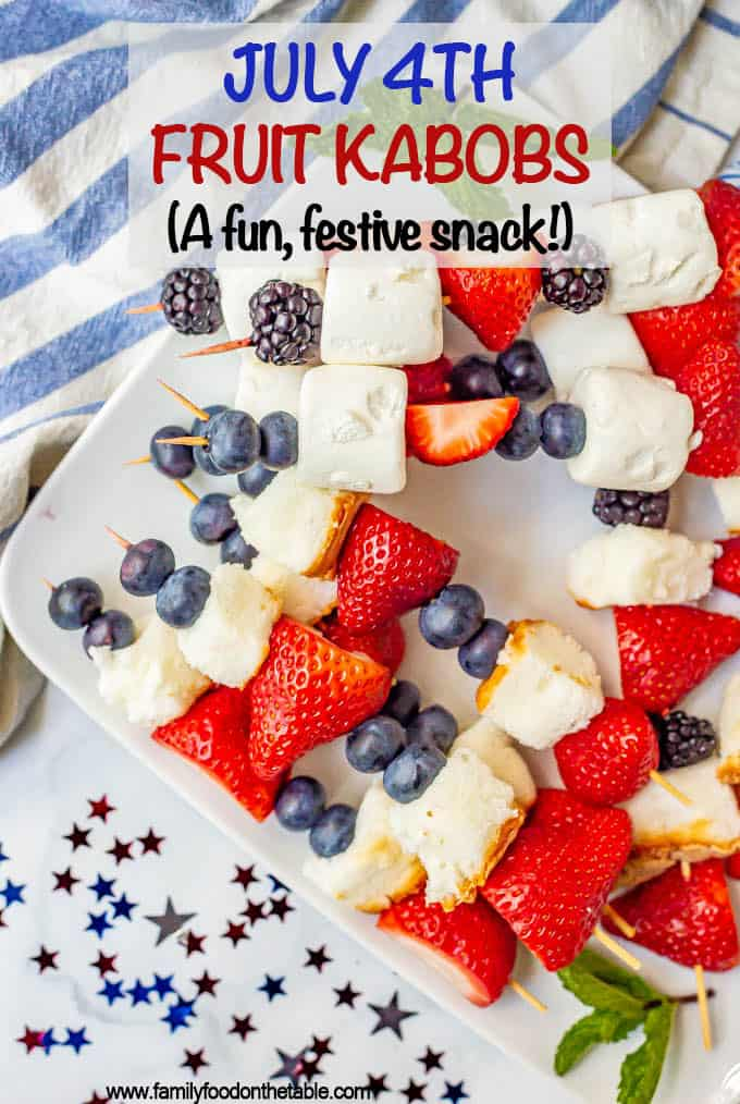 Red white and blue snacks of fruit kabobs on a plate with festive decor nearby
