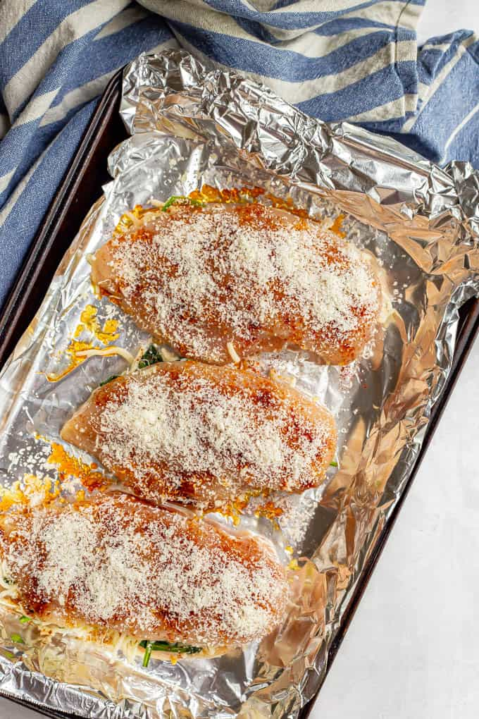 Chicken breasts topped with Parmesan cheese on a foil lined baking pan before baking