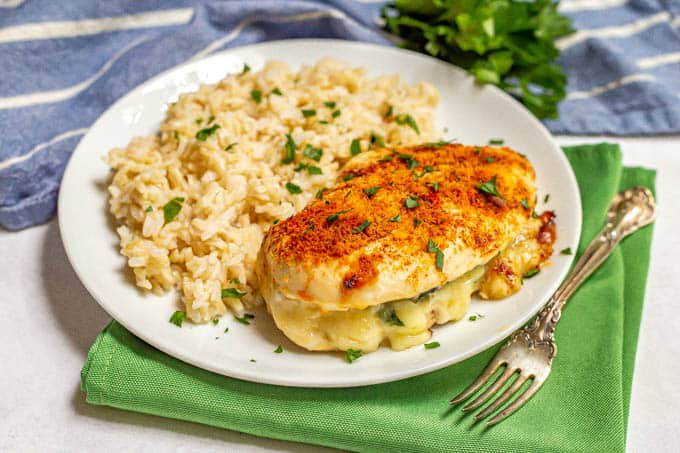 Baked stuffed chicken breast with spinach and mozzarella cheese served with brown rice and topped with fresh parsley