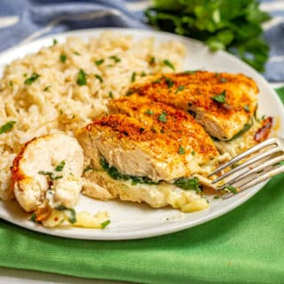 Sliced Parmesan crusted chicken breast stuffed with spinach and mozzarella cheese on a white plate with brown rice with a fork leaning on the plate