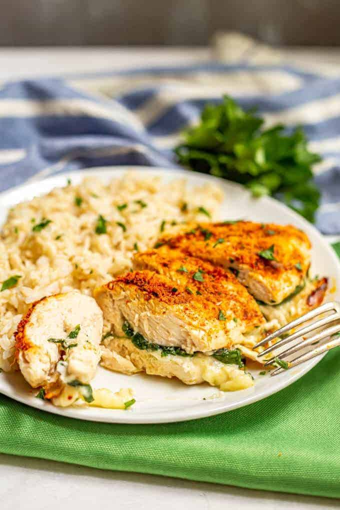 Sliced Parmesan crusted chicken breast stuffed with spinach and mozzarella cheese on a white plate with brown rice and a sprinkling of parsley and a fork nearby
