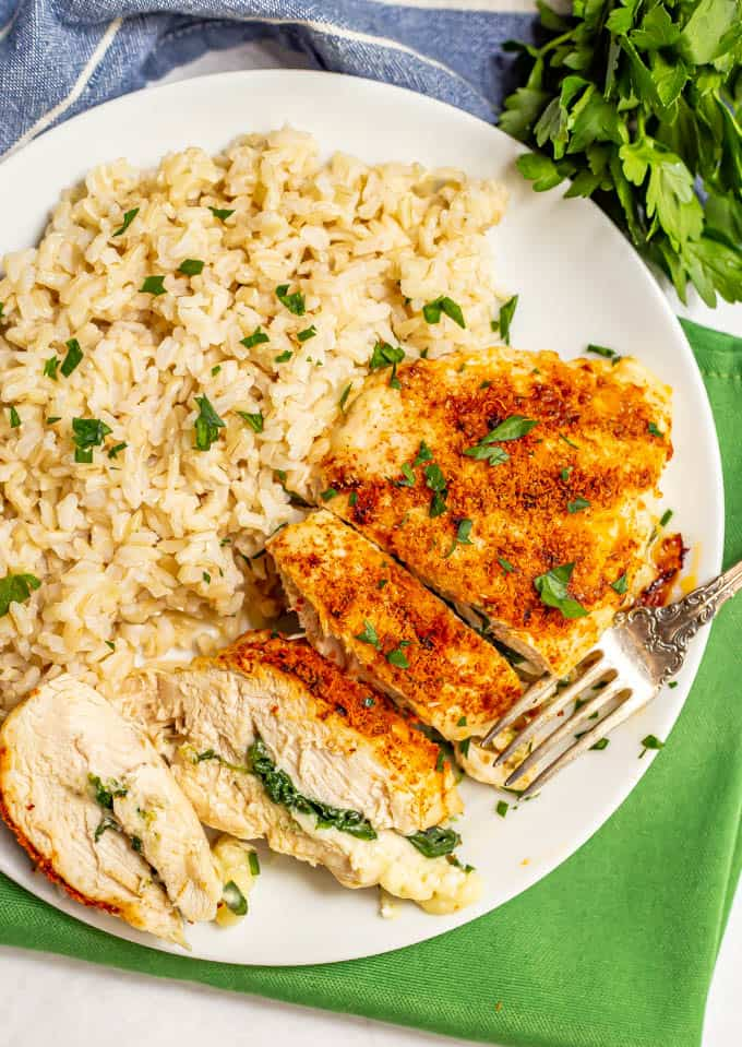 Sliced Parmesan crusted chicken breast stuffed with spinach and mozzarella cheese on a white plate with brown rice and a sprinkling of parsley