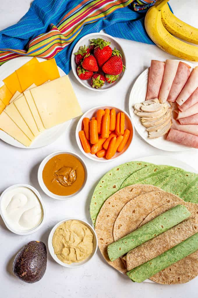 Ingredients laid out for making healthy lunch wraps, including deli meats, sliced cheese, peanut butter, cream cheese, hummus, avocado, banana and an assortment of wraps