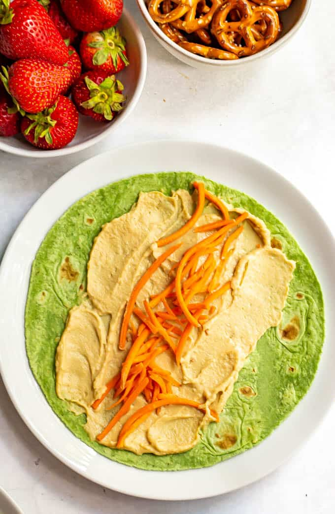 Hummus and shredded carrots on a spinach wrap with bowls of strawberries and pretzels in the background