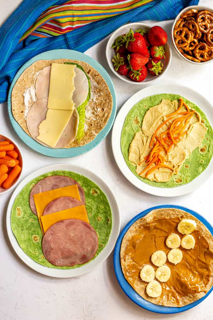 A collection of different healthy lunch wraps open face on plates